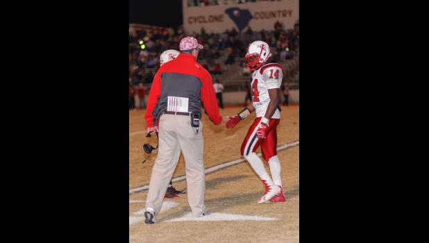 Head Football Coach Andrew Webb congratulates Mark Wise (14) during Friday's playoff game at Chester. Wise had 86 rushing yards and 71 return yards. -- Photo by Fletcher Pruitt Jr.
